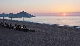 Den sceniska sikten av den privata sandiga stranden på stranden med solen bäddar ned mot havet och bergen Amara Dolce Vita Luxury Arkivbilder