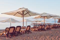 Den sceniska sikten av den privata sandiga stranden på stranden med solen bäddar ned mot havet och bergen Amara Dolce Vita Luxury Arkivfoton