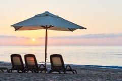 Den sceniska sikten av den privata sandiga stranden på stranden med solen bäddar ned mot havet och bergen Amara Dolce Vita Luxury Royaltyfri Bild