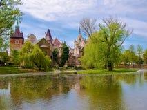Den sceniska sikten av den Vajdahunyad slotten reflekterad i sjön under den blåa himlen i huvudsaklig stad parkerar, Budapest, Un Fotografering för Bildbyråer