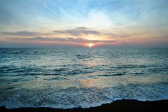 Den sceniska sikten på ett hav och sand sätter på land med färgrik solnedgång royaltyfria bilder