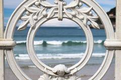 Den sceniska sikten på den San Sebastian stranden och havet med vågor till och med det dekorativa vita järnstaketet inramar, ögon Royaltyfri Foto