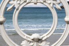 Den sceniska sikten på den San Sebastian stranden och havet med vågor till och med det dekorativa vita järnstaketet inramar, ögon Arkivfoton