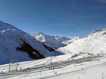 Den schweiziska järnvägsstationen mellan snö täckte kullar i härligt solsken royaltyfri bild