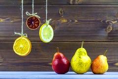 An den Seilscheiben der Zitrone, der Orange und des Kalkes hängen Legen Sie auf dem Tisch reife süße Birnen Lizenzfreie Stockfotos