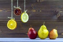 An den Seilscheiben der Zitrone, der Orange und des Kalkes hängen Legen Sie auf dem Tisch reife süße Birnen Stockfotografie