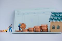 Den selektiva fokusen av miniatyren och bunten av mynt med konto buar Arkivfoto