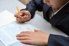 Den selektiva fokusen av pysen som lär hur man skriver hans namn, ungestudie hemma, barn gör läxa hemma, begreppet för litet barn arkivbild