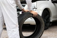 Den selektiva fokusen på händer av den yrkesmässiga mekanikern i enhetlig innehavskiftnyckel och gummihjulet på reparationen park arkivfoto