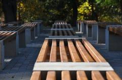 Den selektiva fokusen på träbänkar för enkel design i stad parkerar royaltyfri bild