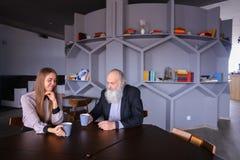 Den Senescent mannen mötte med kvinnlig anställd för kopp te under bre fotografering för bildbyråer