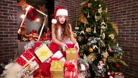 Den sexiga älvan tillfogar gåvor för ` s för det nya året, flicka i jultomten hatten för ` som s förbereder ferieaskar för jul, m arkivfilmer