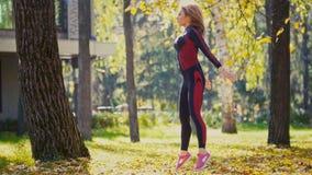 Den sexiga attraktiva kvinnliga blonda bikini-kondition modellen som sträcker i hösten, parkerar på jordning täckte gula sidor -  Arkivbilder