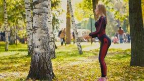 Den sexiga attraktiva kvinnliga blonda bikini-kondition modellen som sträcker i hösten, parkerar på jordning täckte gula sidor -  Royaltyfri Foto