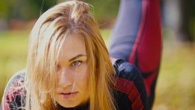 Den sexiga attraktiva kvinnliga blonda bikini-kondition modellen som sträcker i hösten, parkerar upp - benelevatorer, slut Arkivbilder