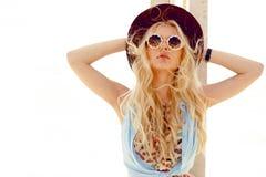 Den sexiga blonda flickan med rund solglasögon, grov bomullstvillskjortan, den gulliga klänningen, våghår och den burgundy hatten fotografering för bildbyråer
