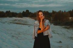 Den sexiga blonda haired unga kvinnan som poserar i sander av öknen, tände vid rött ljus för inställningssolen Arkivfoton