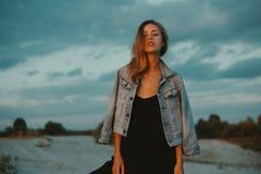 Den sexiga blonda haired unga kvinnan som poserar i sander av öknen, tände vid rött ljus för inställningssolen Royaltyfria Foton