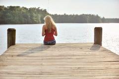 Den sexiga blonda kvinnan fiskar från skeppsdocka Royaltyfria Bilder