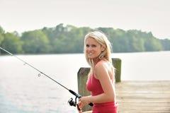 Den sexiga blonda kvinnan fiskar från skeppsdocka Fotografering för Bildbyråer