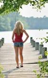 Den sexiga blonda kvinnan fiskar från skeppsdocka Arkivfoto