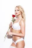 Den sexiga blonda kvinnan i underkläderinnehav steg Arkivbild