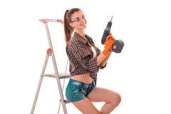 Den sexiga brunettdamen gör för att renovera en lägenhet med borrar in händer och stegen som isoleras på vit bakgrund i studio royaltyfria bilder