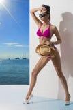 Den nätt brunetten med bikinin och beväpnar på bekläda Fotografering för Bildbyråer