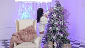 Den sexiga brunettflickan dekorerar julgranen lager videofilmer