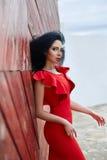 Den sexiga brunettkvinnan i en röd klänning står nära den röda porten Royaltyfria Foton