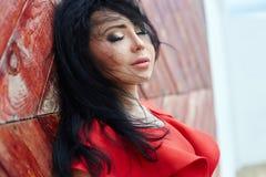 Den sexiga brunettkvinnan i en röd klänning står nära den röda porten Royaltyfria Bilder