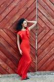 Den sexiga brunettkvinnan i en röd klänning står nära den röda porten Royaltyfri Fotografi