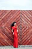 Den sexiga brunettkvinnan i en röd klänning står nära den röda porten Arkivbild