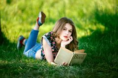 Den sexiga caucasian unga flickan läste boken som ligger på grönt gräs Arkivfoton