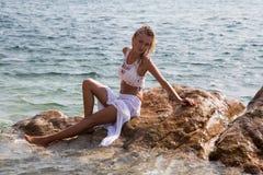 Den sexiga damen i våt vit snör åt klänningen på stenig kust Fotografering för Bildbyråer