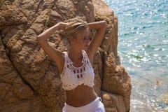 Den sexiga damen i vit snör åt klänningen på den steniga stranden Arkivfoto