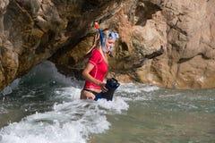 Den sexiga dykareflickan ser in grottan att förbereda hennes dyk royaltyfria foton