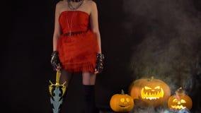 Den sexiga förföriska jäkelflickan flörtar, blinkningar, firar halloween med läskiga roliga pumpor i mörker Demonkvinna med stock video