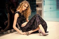Den sexiga flickan i aftonklänning sitter på golvet, mode royaltyfri foto