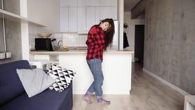 Den sexiga flickan i hennes 20 ` s dansar i hennes hemtrevliga lägenhet som tycker om ungdom lager videofilmer