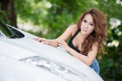 Den sexiga flickan i svart väst poserar på huvbilen royaltyfri fotografi