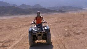 Den sexiga flickan på en kvadratcykel rider till och med öknen av Egypten på bakgrund av berg l?ngsam r?relse stock video