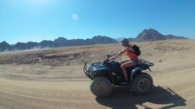 Den sexiga flickan rider en kvadratcykel i öknen av Egypten Dynamisk sikt i rörelse stock video