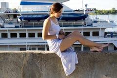Den sexiga flickan sitter på bakgrund av ett skepp Royaltyfri Foto