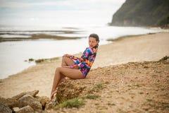 Den sexiga flickan som poserar sammanträde vaggar på, på stranden royaltyfri bild