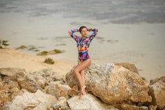 Den sexiga flickan som poserar sammanträde vaggar på, på stranden arkivfoton