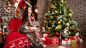 Den sexiga flickan väntar nytt år, den charmiga kvinnan nära julgranen och gåvor, kvinna i festlig klänning på julafton arkivfilmer