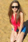 Den sexiga härliga flickan med lång bärande solglasögon för mörkt hår som sitter i grov bomullstvill, kortsluter på stranden nära Royaltyfria Bilder