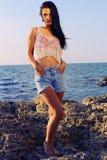 Den sexiga härliga kvinnan bär en överkant med jeanskortslutningar och poserastranden Royaltyfria Foton