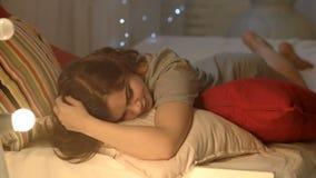 Den sexiga, härliga och romantiska flickan ligger på sängen Den unga kvinnan lägger ner på sängen Kvinnan lägger ner för att vila arkivfilmer